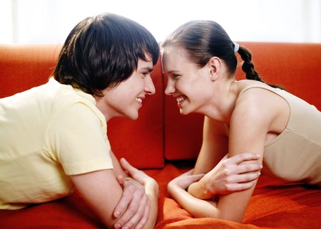 Couple lying on the couch facing each other Stock Photo