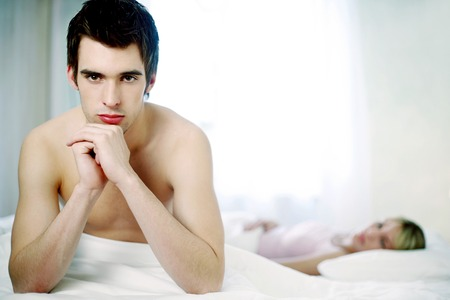 Man sitting on the bed sulking Stock Photo
