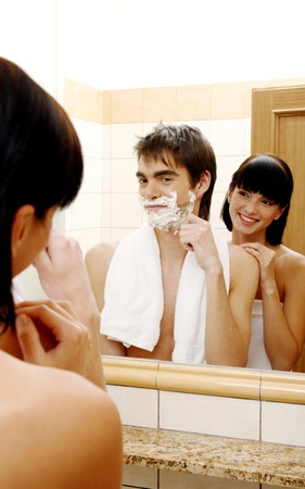 Woman watching her husband shaving photo