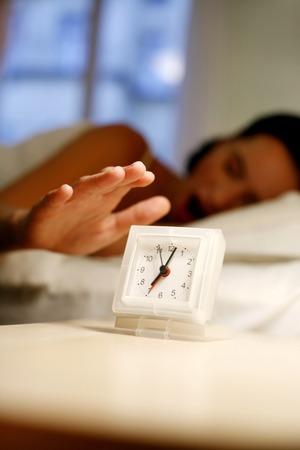 Woman yawning while turning off the ringing alarm clock photo