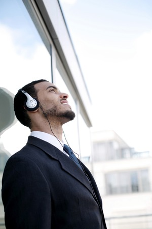 gratified: Businessman listening to music on the headphones