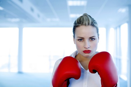 Businesswoman wearing red boxing gloves