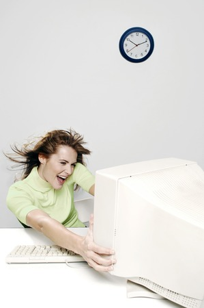 Businesswoman being blown away by a computer desktop photo