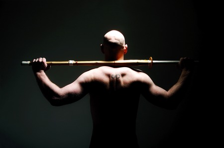 sword act: Back shot of shirtless man holding sword