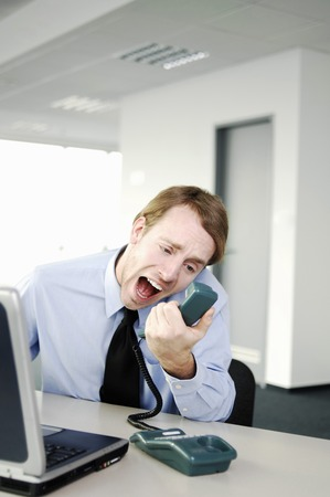 Businessman screaming into the phone receiver photo