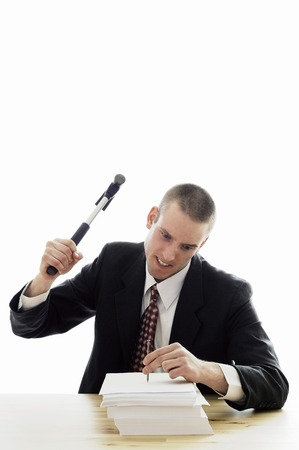 Businessman hammering a nail into a stack of papers Stock Photo