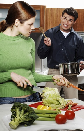 Couple arguing while cooking in the kitchen photo