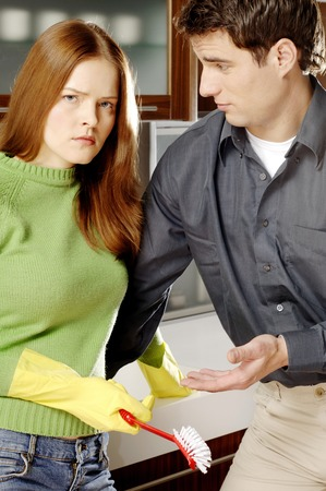 Man consoling his angry girlfriend in the kitchen