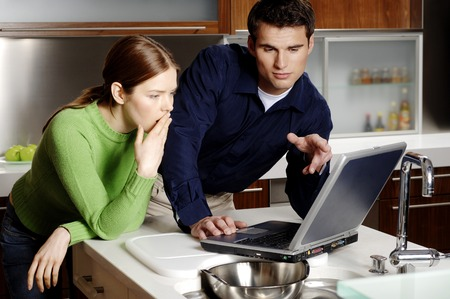 Couple using laptop in the kitchen photo