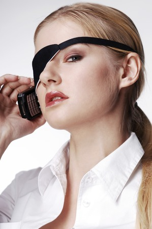Businesswoman with eye patch talking on the cell phone photo