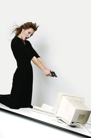 Businesswoman pointing her pistol at a computer monitor photo