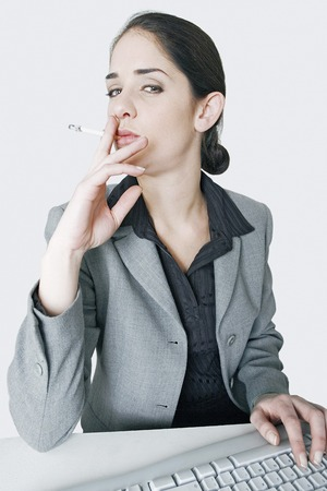 Businesswoman smoking cigarette while doing her work photo