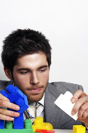 plastic bricks: Businessman playing with colourful plastic bricks Stock Photo