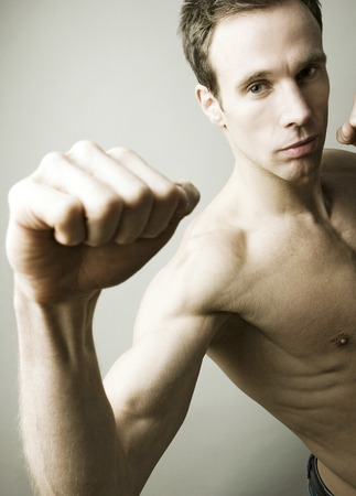 Shirtless man striking a kung fu pose for the camera photo