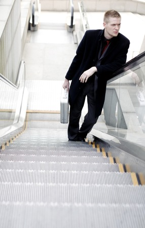 Businessman standing on an escalator photo