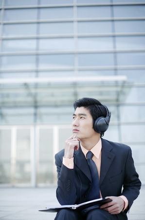 desirous: Businessman listening to music on the headphone