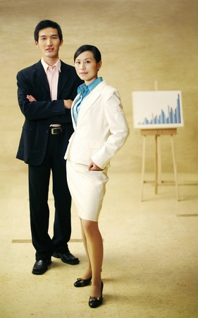 desirous: Businessman and businesswoman posing near a chart Stock Photo