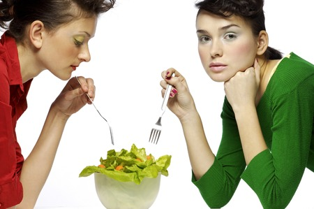 Two women sharing a bowl of salad photo