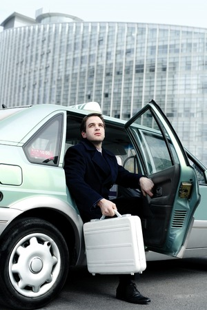 desirous: Businessman coming out from a taxi Stock Photo