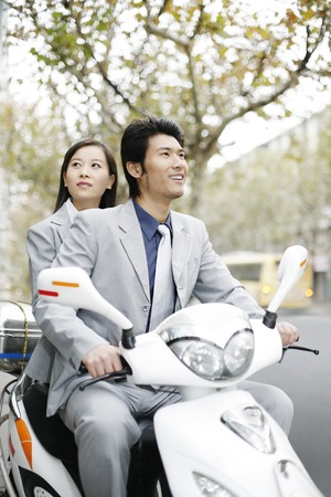 Businessman and businesswoman riding on a scooter photo