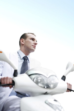Businessman riding on a scooter photo