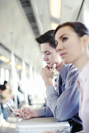 Businessman text messaging in the train photo