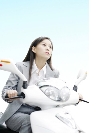 Businesswoman riding on a scooter photo