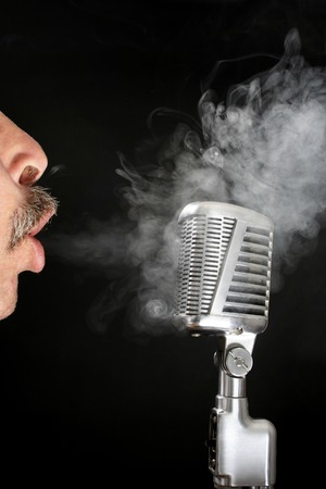 Man blowing cigarette smoke at a microphone