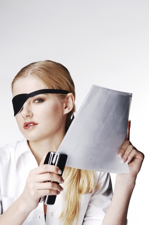 Businesswoman with eye patch stapling papers photo