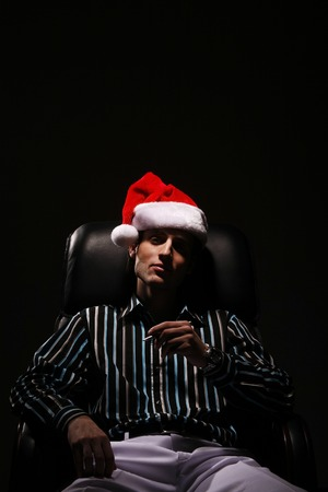 Businessman with Christmas hat smoking cigarette photo