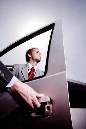 abriendo puerta: Mano que abre la puerta del coche para un hombre de negocios Foto de archivo