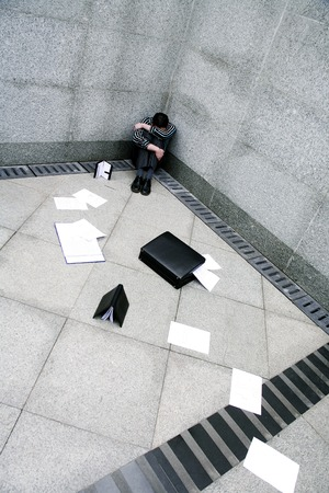 Businessman sitting at the corner of a building photo