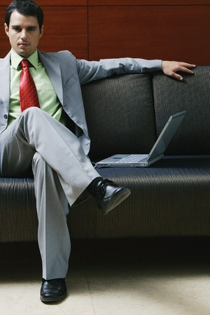 Businessman sitting on the couch with a laptop beside him photo