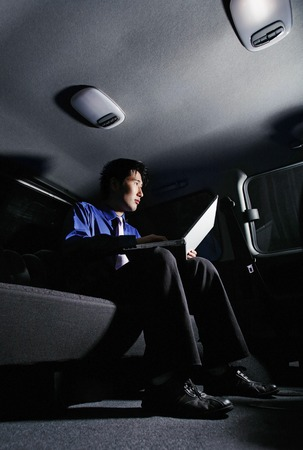desirous: Businessman using laptop in the car