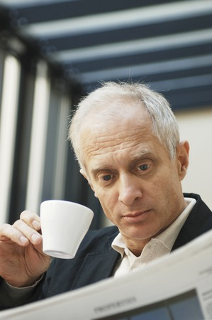 desirous: Businessman drinking coffee while reading newspaper