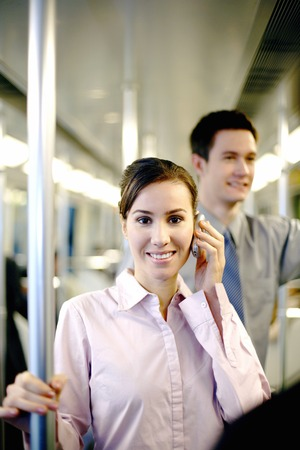 Businesswoman talking on the hand phone in the train photo