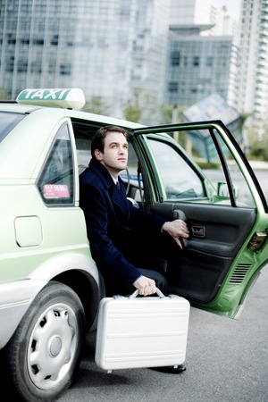 Businessman getting out from a taxi photo