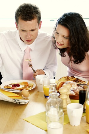 Couple reading newspaper while having breakfast together photo