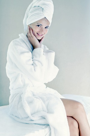 Woman in bathrobe with towel wrapped hair photo