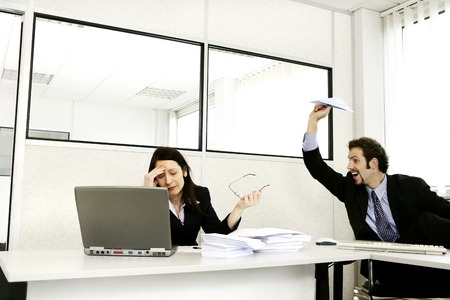 Businessman throwing a paper plane at his stressed up colleague photo