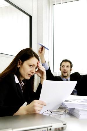 personen: Zakenman spelen met papieren vliegtuig, terwijl zijn collega is druk aan het werk