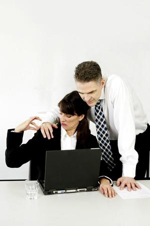 Businessman taking advantage of his female colleague Stock Photo