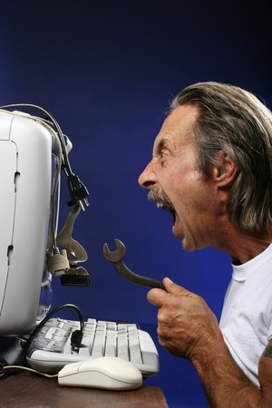 Man getting frustrated while fixing his computer photo