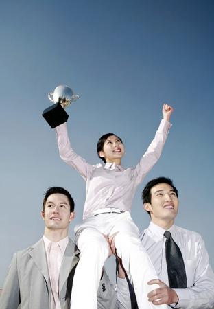Businessmen lifting up a female winner photo