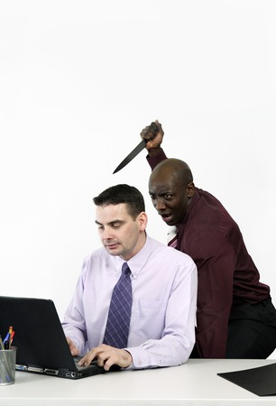 Businessman trying to stab his colleague with a knife photo