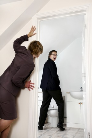 embarrassing: Businesswoman peeping her male colleague in the toilet Stock Photo