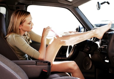 Woman shaving her leg in the car