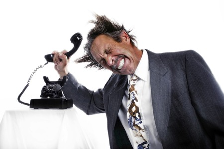Businessman knocking his head with a phone receiver