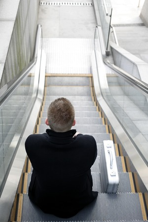 Businessman sitting on a moving escalator photo