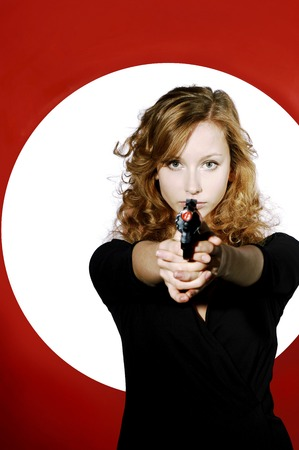 Businesswoman aiming a pistol at the camera photo
